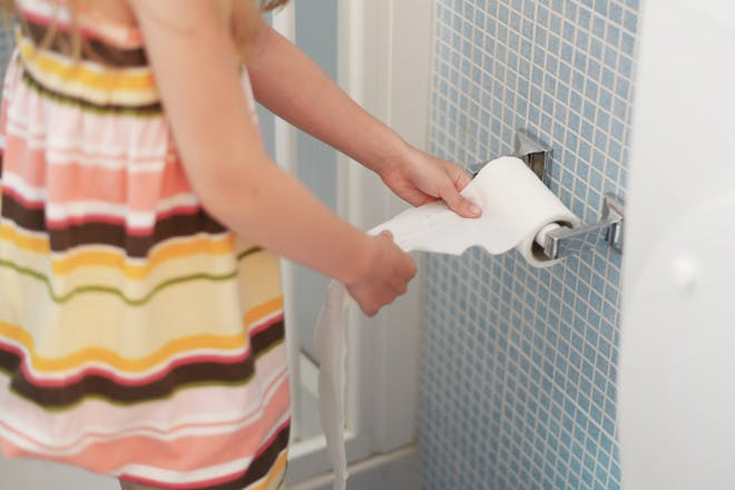 child getting toilet paper from the roll