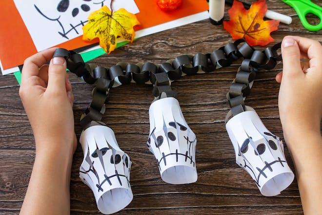 Halloween craft activity making paper skeleton lanterns and black paper chain