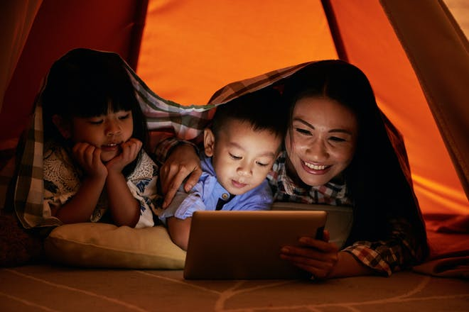 Mum and toddler boy and girl watch a film in a blanket fort