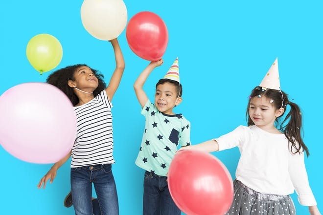 Three young children playing with balloons and wearing party hats