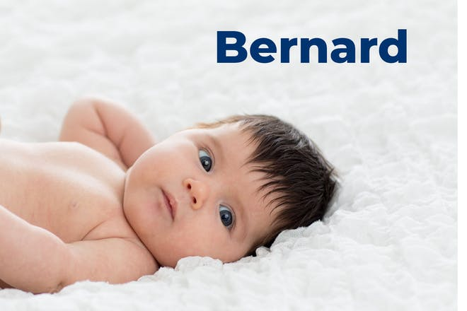 Baby with black hair lying down. Name Bernard written in text