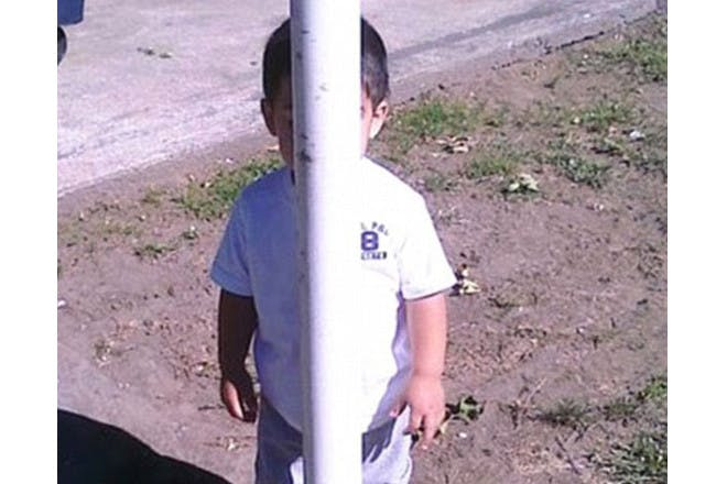 child hiding behind pole