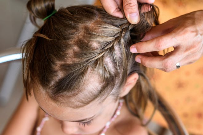 A little girl getting her hair braided by an adult