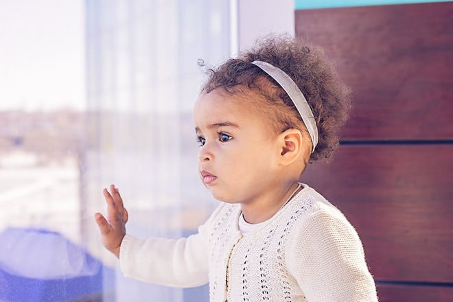 Mixed race toddler looking out of the window