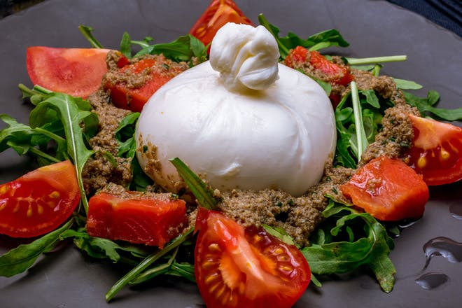 Burrata cheese with sliced tomatoes, rocket and pesto