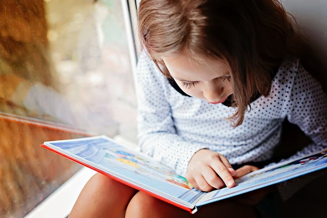 Young girl reading by window