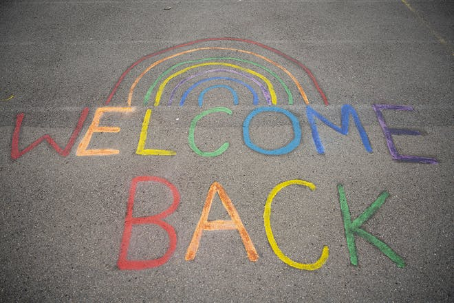 The words welcome back and a rainbow drawn on school playground
