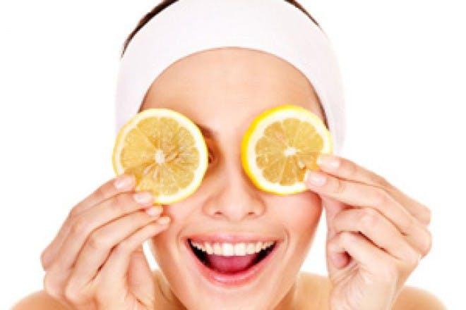 woman holding lemon slices to eyes