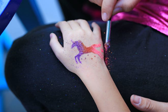 Child with a glittery unicorn tattoo