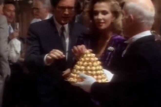 A still from a vintage Ferrero Rocher TV advert, with party guests taking chocolates