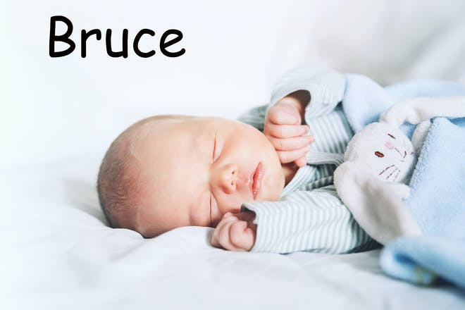 A baby sleeping with the name Bruce written in text