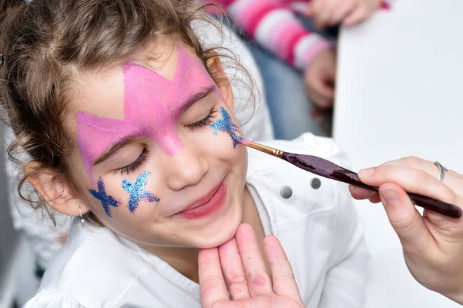 A little girl having her face painted