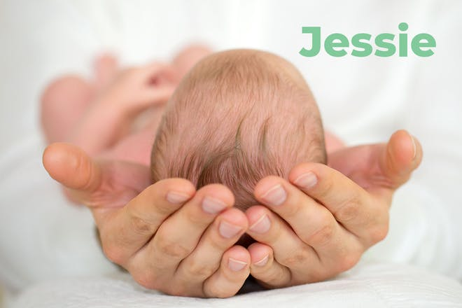 Top of baby's head being cradled by adult hands. Name Jessie written in text