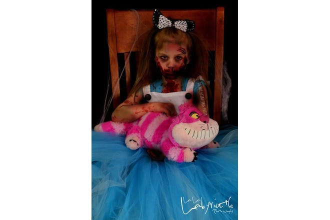girl dressed as alice in wonderland made to look like a zombie