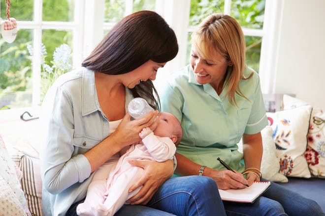Women bottle feeding baby while health visitor takes notes