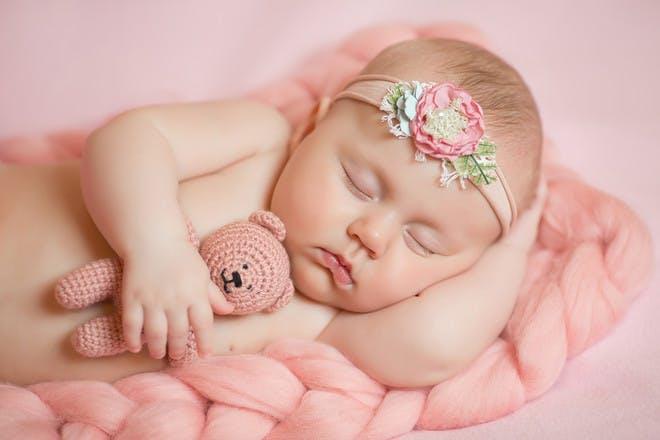 Baby girl sleeping with pink teddy