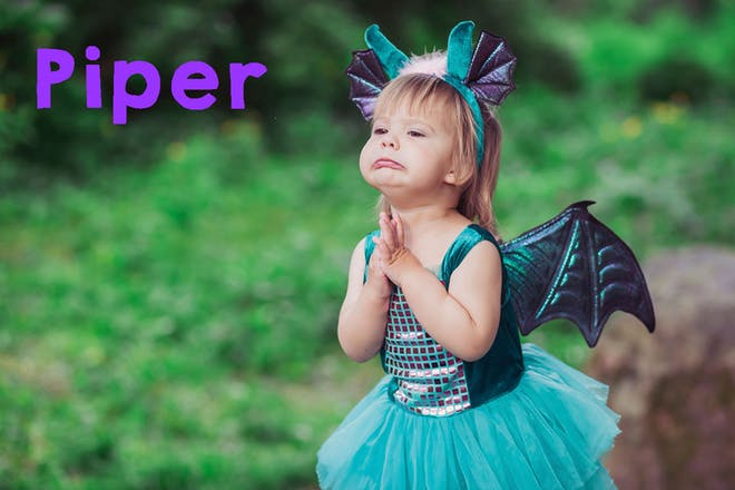 Toddler girl in dragon outfit. Text says Piper