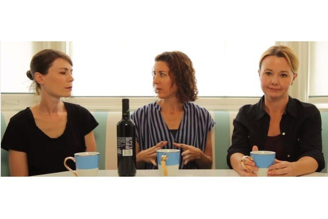 Three mums talking at kitchen table