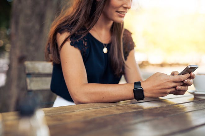 woman sitting at table outside and texting on her mobile