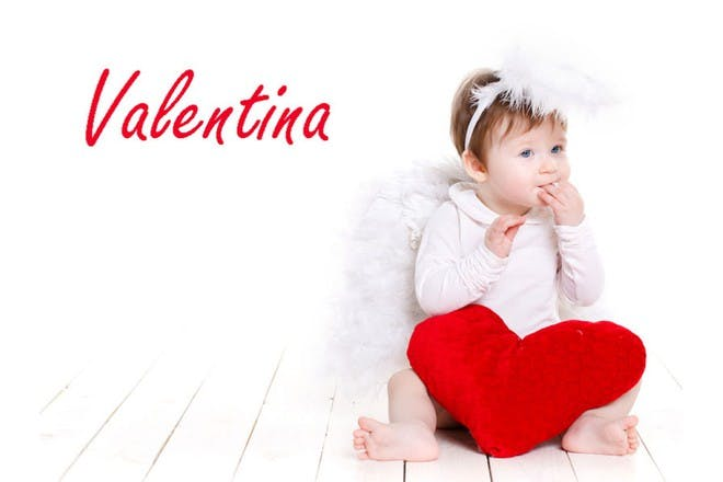 baby in wings and halo with heart pillow