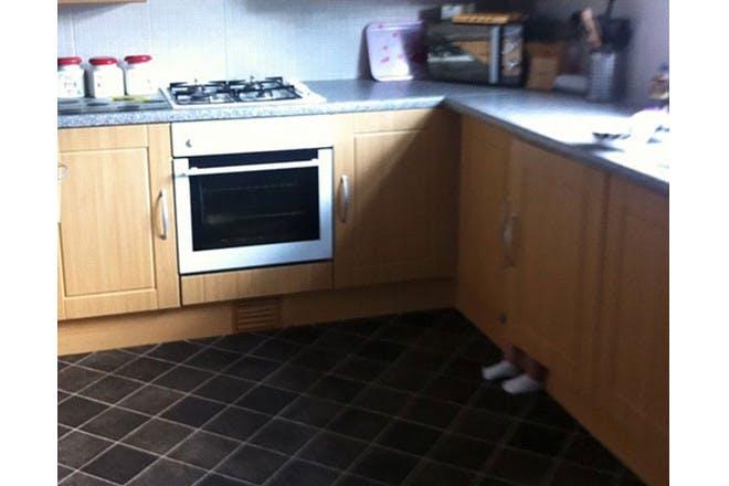 child hiding in kitchen cupboard