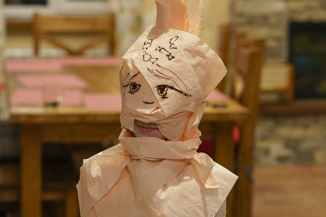 A toddler dressed as a mummy wrapped in toilet roll bandages for Halloween