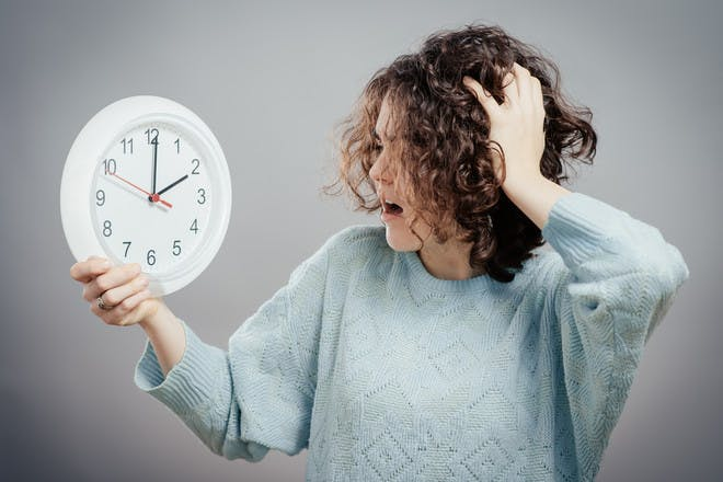 Woman looking at clock with horror