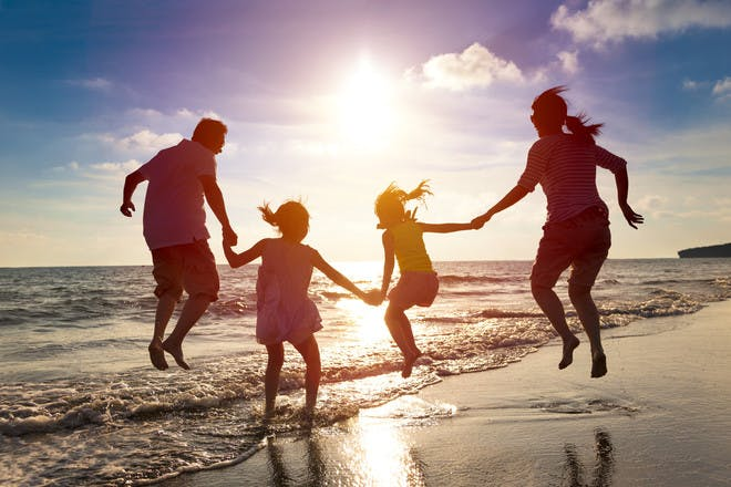 family jumping in the surf of the ocean with the sun behind them