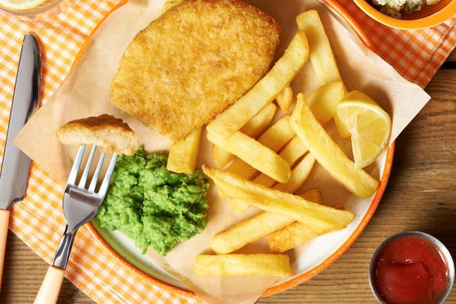 Vegan fish fillet on a plate with chips, a slice of lemon and mushy peas