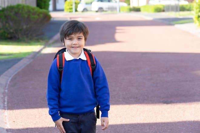 Little boy smiling wearing school uniform