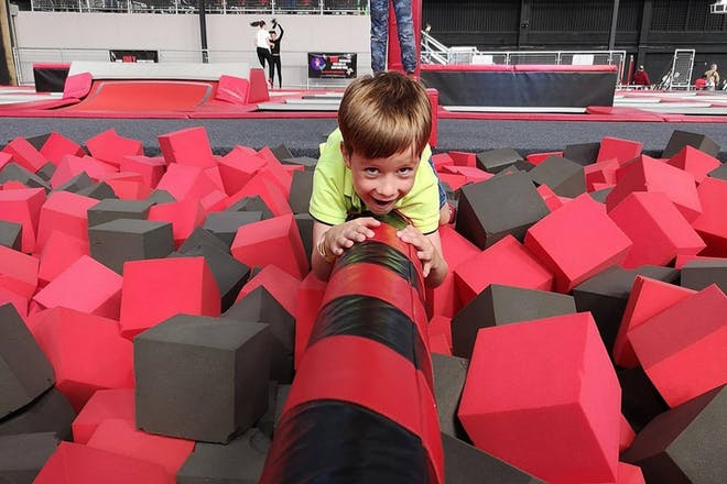Boy crawling over balance beam across foam pit