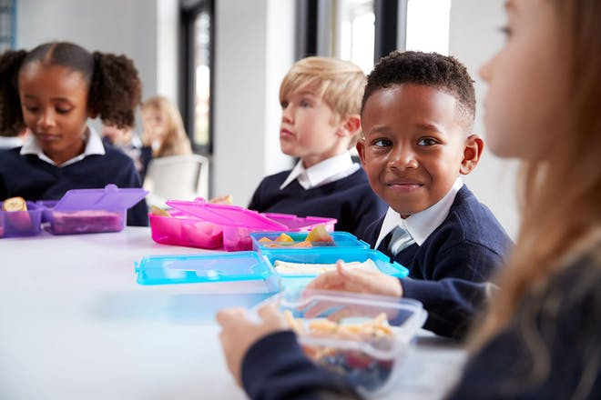 Primary school children at a table with lunch boxes