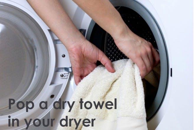 hands putting blanket in dryer