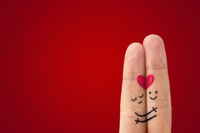 Fingers with smiley faces hugging with a love heart