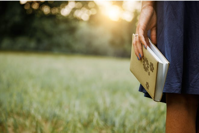 woman holding journal standing in field