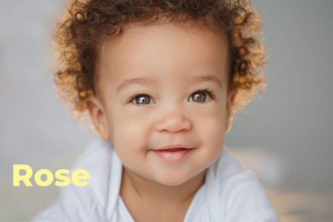 baby with curly hair. Name Rose written in text