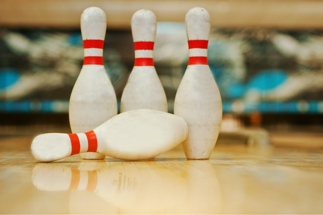 Four white and red bowling pins at a bowling alley