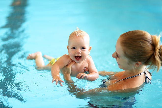 Happy baby with mum in swimming pool