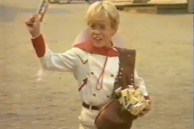The Milky Bar kid from the retro Milky Bar TV adverts. Blonde boy waves a Milky Bar chocolate bar around.