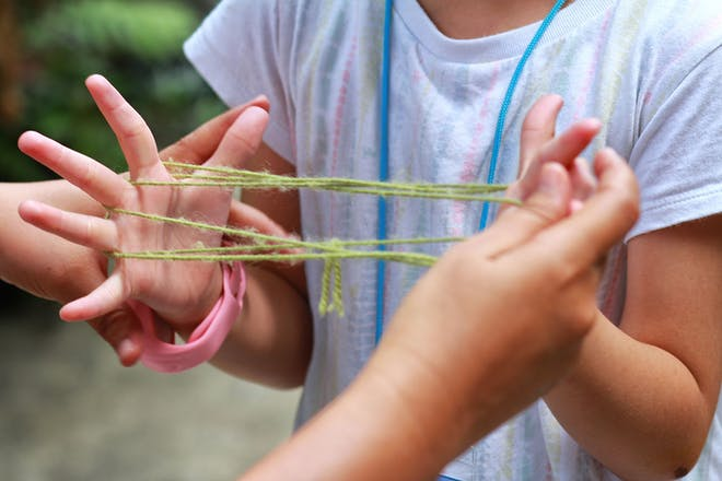 Two girls playing cat's cradle with a piece of wool