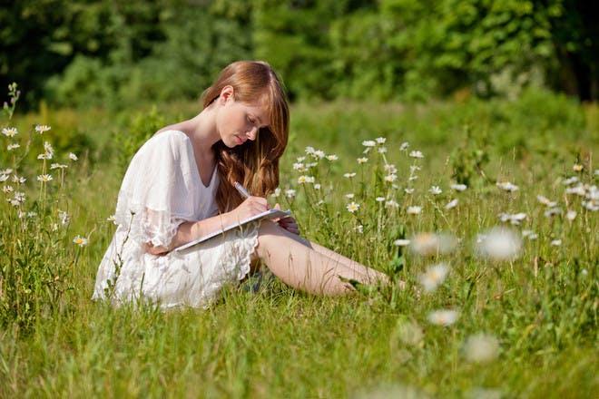 Woman writing in field