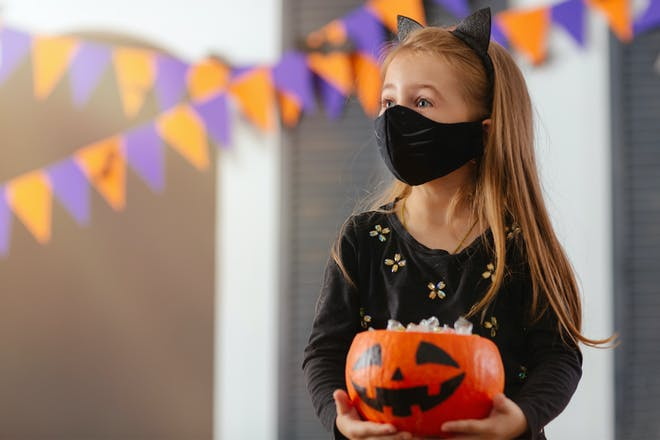 Girl dressed in Halloween costume with a mask on holding a pumpkin