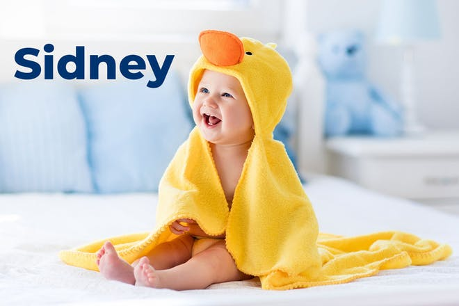 Baby wearing duck towel. Name Sidney written in text