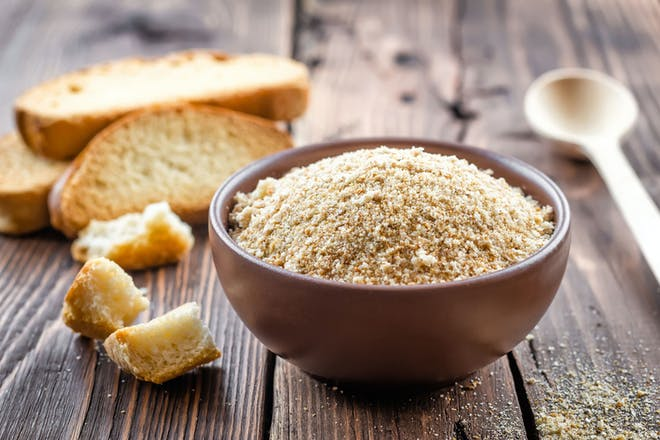 Bowl of breadcrumbs on wooden table with wooden spoon and bread slices behind