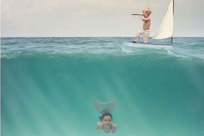girl as mermaid in water with boy in boat
