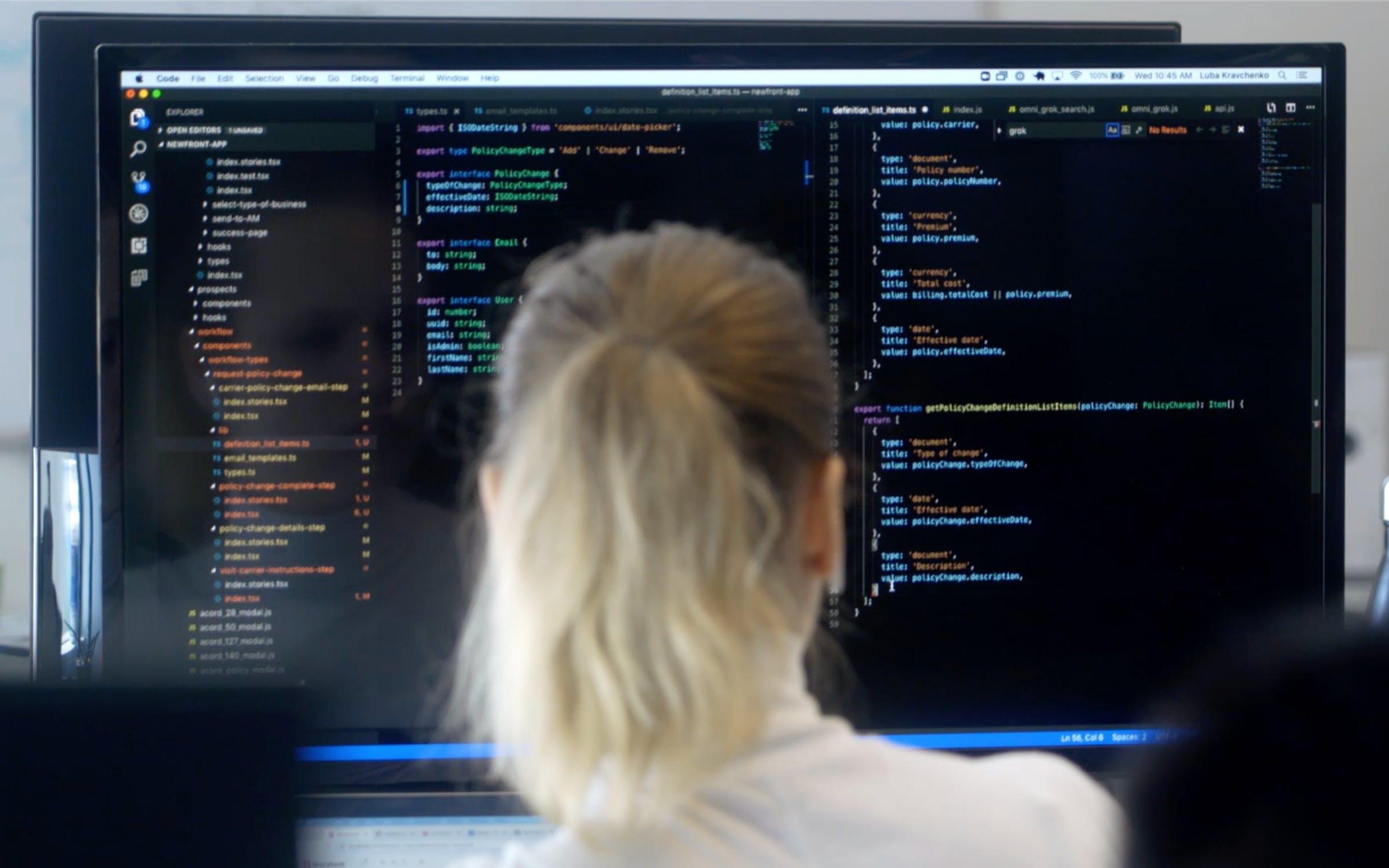 Woman looking at computer screen displaying coding