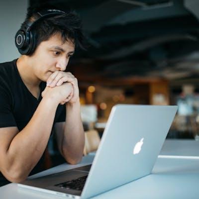 Junge sitzt konzentriert vor Laptop