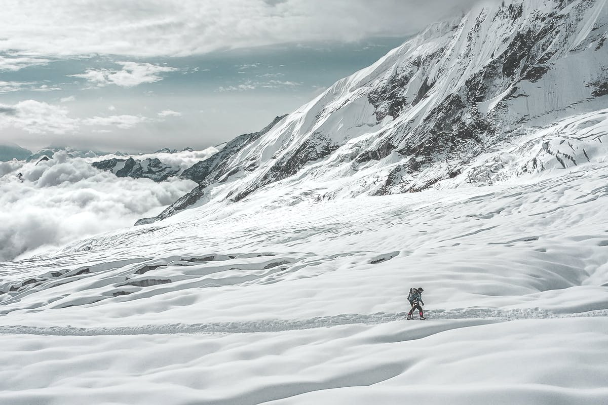 Nims walking alone across a snow filled valley