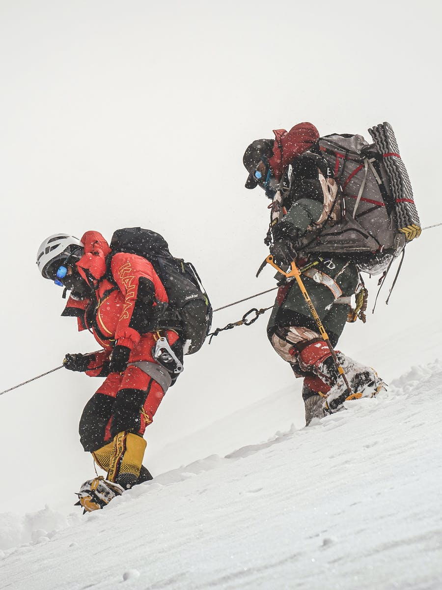 Nims clipped to his client and rope descend the mountain