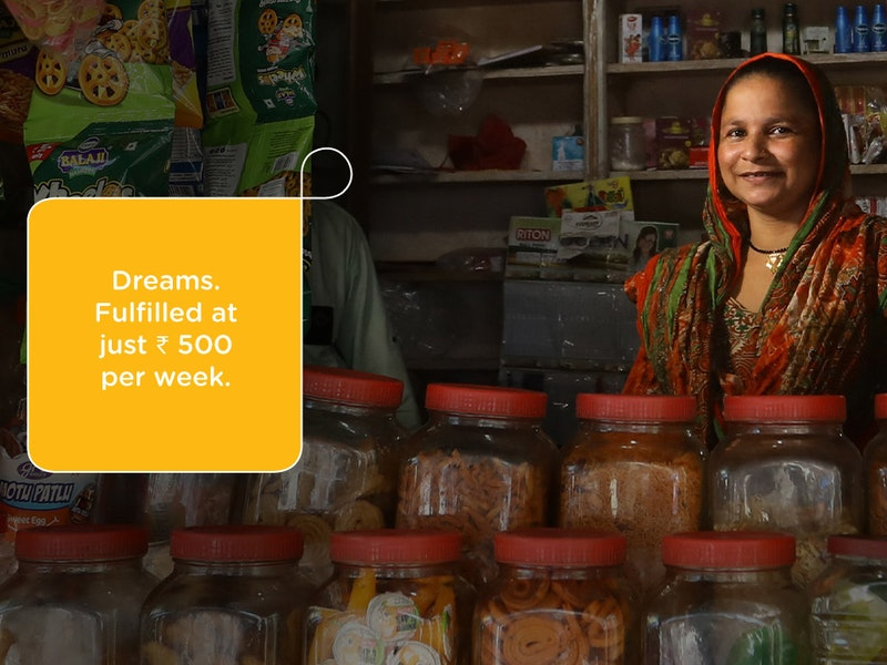 A smiling woman stands behind jars of food in her store.